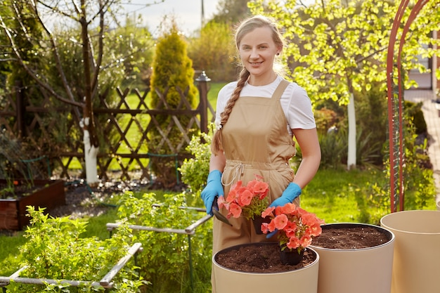 A young beautiful female gardener transplants flowers into large ceramic vases in the garden.