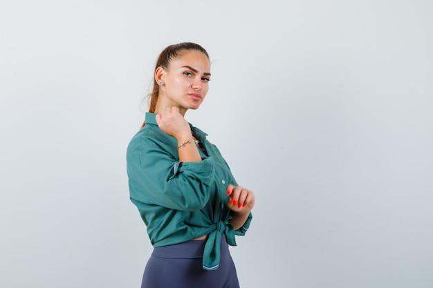 Giovane bella donna in camicia verde in posa tenendo la mano vicino al viso e guardando beata, vista frontale.