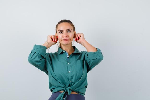Giovane bella femmina in camicia verde che tira giù i lobi delle orecchie e sembra triste, vista frontale.