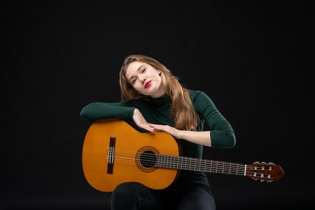 Молодая красивая гитаристка держит свой любимый музыкальный инструмент на темноте