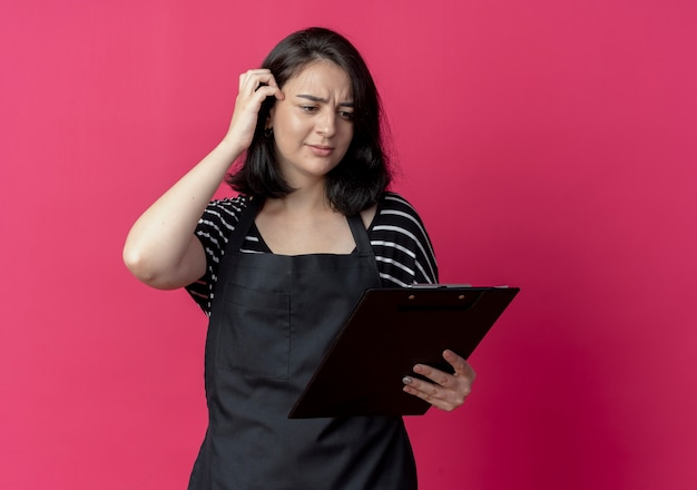 Young beautiful female hairdresser in apron holding clipboard looking at it confused over pink