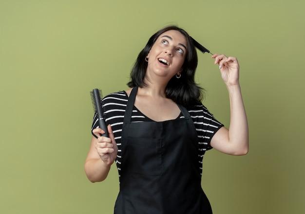 Giovane bella donna parrucchiere in grembiule che tiene le spazzole per capelli sorridendo allegramente con la faccia felice in piedi sopra la parete chiara