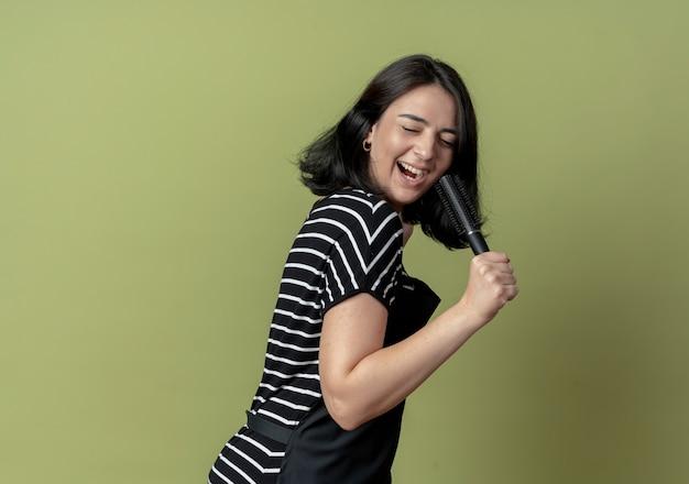 Giovane bella donna parrucchiere in grembiule tenendo le spazzole per capelli sorridente allegramente con la faccia felice utilizzando la spazzola per capelli come microfono cantando in piedi sopra la parete chiara