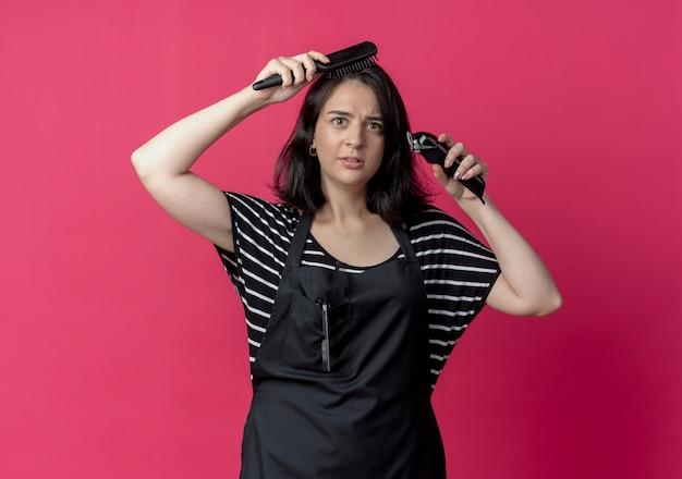 Giovane bella donna parrucchiere in grembiule che tiene macchina per il taglio dei capelli che pettina i capelli con la spazzola in piedi sopra la parete rosa