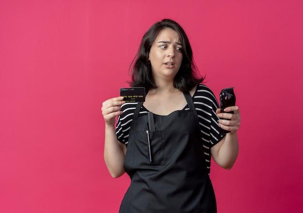 Giovane bella donna parrucchiere in grembiule che tiene macchina per il taglio dei capelli e carta di credito che sembra confusa e molto ansiosa sul rosa