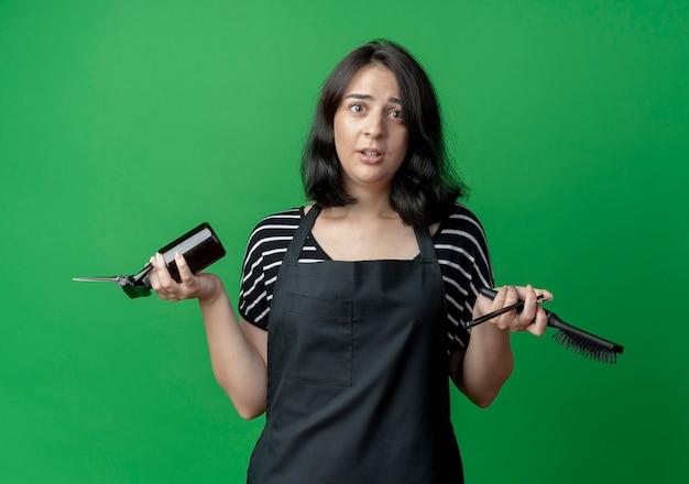 Giovane bella donna parrucchiere in grembiule che tiene forbici spray e pennello confuso in piedi sopra la parete verde