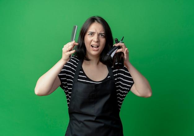 Giovane bello parrucchiere femminile in grembiule che tiene pettine spray e rasoio dispiaciuto e frustrato sul verde