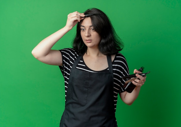 Young beautiful female hairdresser in apron holding spray and razor combing her hair  over green