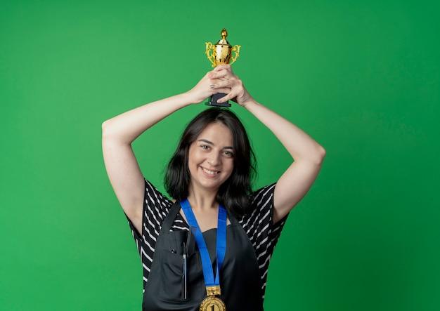 Giovane bello parrucchiere femminile in grembiule che tiene il trofeo sopra il suo odio felice ed eccitato sul verde