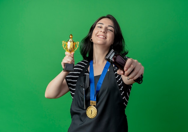 Young beautiful female hairdresser in apron holding trophy and trimmer happy and excited standing over green wall