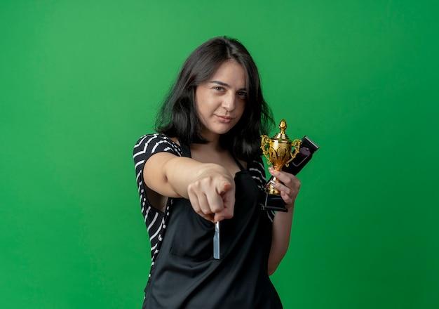 Giovane bella donna parrucchiere in grembiule azienda trofeo e trimmer puntando con il dito alla fotocamera con espressione scettica su verde