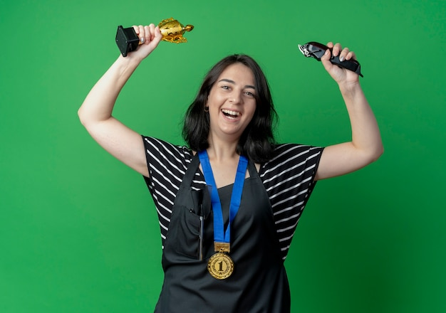 Young beautiful female hairdresser in apron holding trophy and trimmer smiling cheerfully ahppy and excited  over green