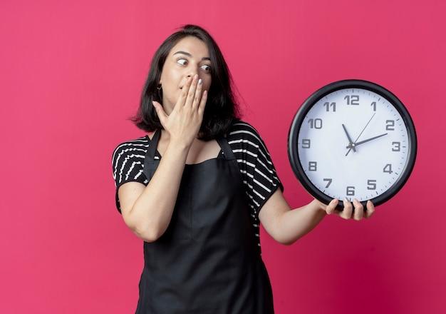 Giovane bella donna parrucchiere in grembiule tenendo l'orologio da parete che copre la bocca con la mano che è scioccata sul rosa