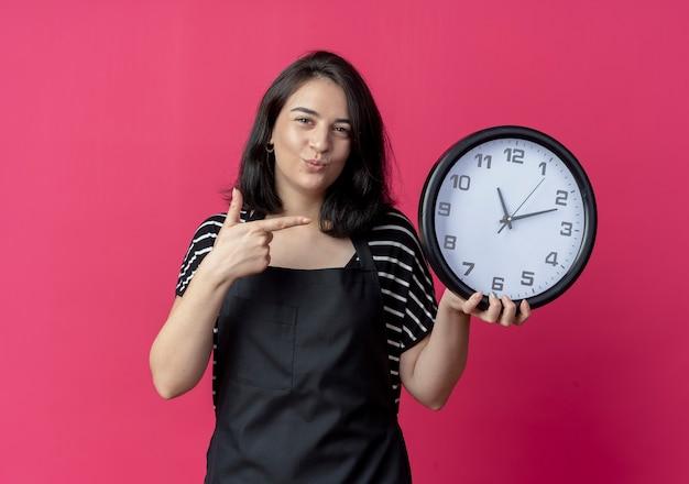 Giovane bella donna parrucchiere in grembiule tenendo l'orologio da parete che punta con il dito sorridendo su rosa