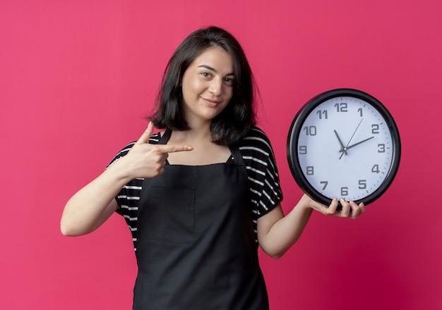 Giovane bella donna parrucchiere in grembiule tenendo l'orologio da parete che punta con il dito sorridendo in piedi sopra la parete rosa