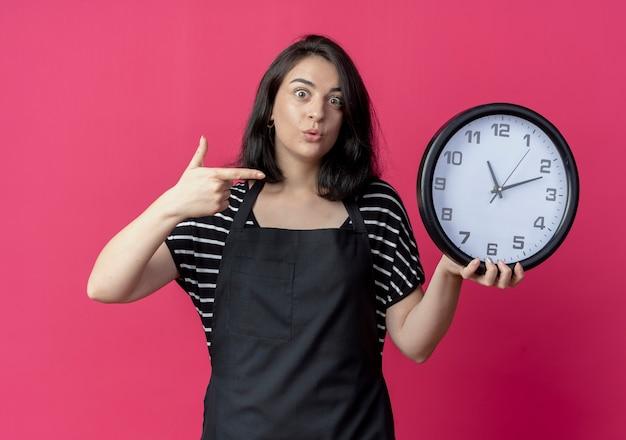 Giovane bella donna parrucchiere in grembiule azienda orologio da parete rivolto con indice figner a guardare sorpreso standinh oltre il muro rosa