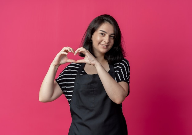 Young beautiful female hairdresser in apron making heart gesture with fingers over chest smiling over pink