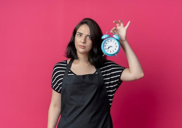 Giovane bella donna parrucchiere in grembiule che mostra sveglia preoccupato in piedi sopra la parete rosa
