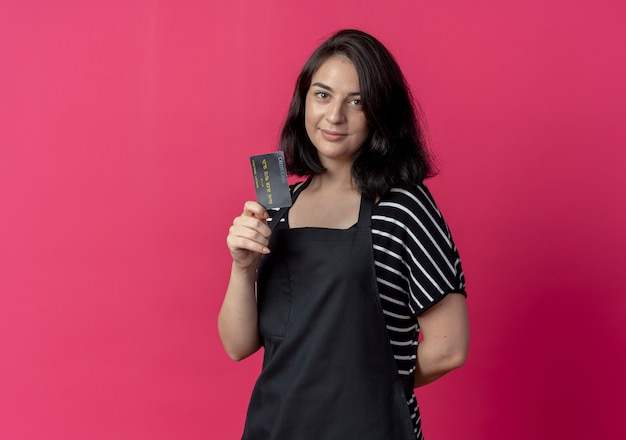 Young beautiful female hairdresser in apron showing credit card lookign at camera smiling over pink