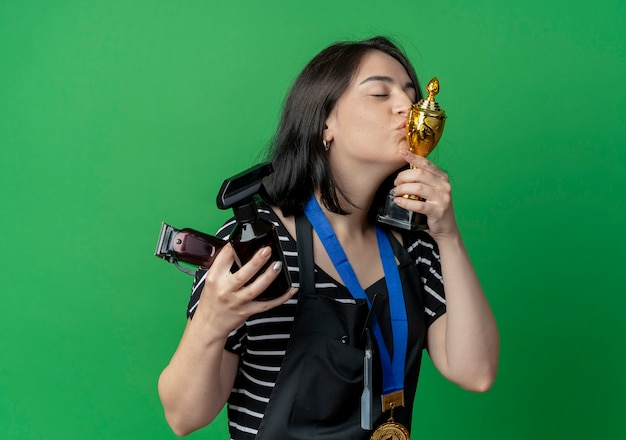 Young beautiful female hairdresser in apron with gold medal around neck holding trophy kissing it with closed eyes standing over green wall
