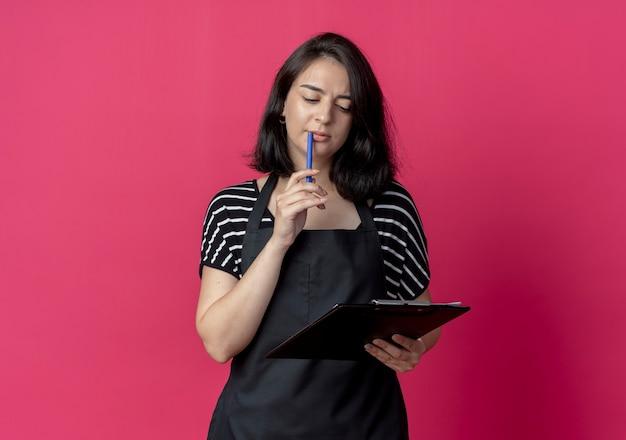 ピンクの上に困惑しているペンでクリップボードを保持しているエプロンの若い美しい女性美容師