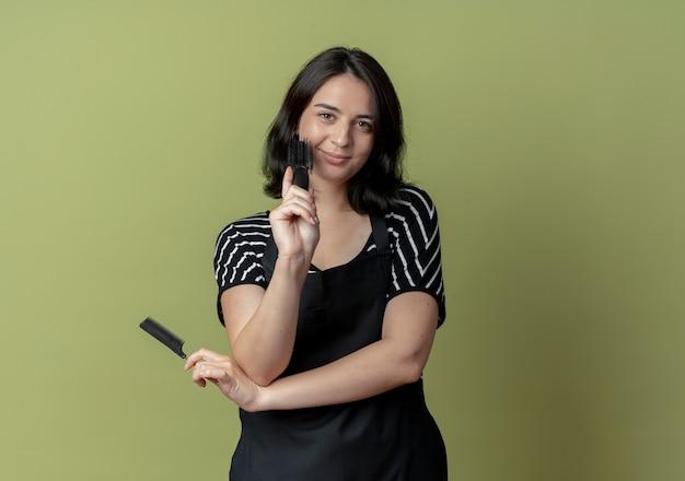 Молодая красивая женщина-парикмахер в фартуке держит расчески с улыбкой на лице, стоя над светлой стеной