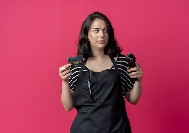 バリカンとクレジットカードを保持しているエプロンの若い美しい女性の美容師はピンクに戸惑いながら脇を見て