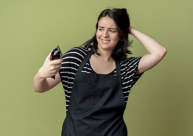 それを見てヘアカッティングマシンを保持しているエプロンの若い美しい女性の美容師は、光で混乱しています