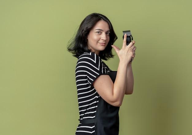 Молодая красивая женщина-парикмахер в фартуке, держащая машину для стрижки, стоя боком, уверенно смотрит на светлую стену