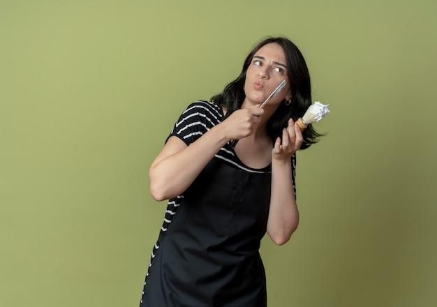 앞치마에 젊은 아름다운 여성 미용사 면도칼을 들고 거품이있는 면도 브러시는 가벼운 벽에 서있는 그녀의 얼굴을 면도 할 것입니다.