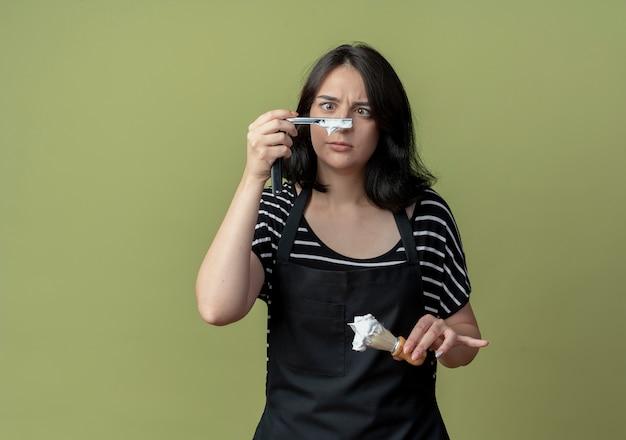 앞치마에 젊은 아름다운 여성 미용사 면도칼을 들고 거품이있는 면도 브러시가 가벼운 벽 위에 서있는 혼란스러운 표정으로 면도기를보고 있습니다.