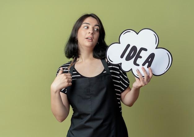 Молодая красивая женщина-парикмахер в фартуке с ножницами и пустым речевым пузырем подписывает слово идеи, смущенное стоя над светлой стеной