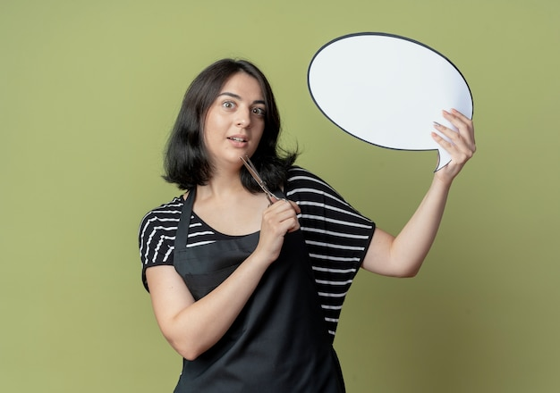 Молодая красивая женщина-парикмахер в фартуке, держащая ножницы, пустой речевой пузырь, смущенный и неуверенный, стоит над светлой стеной
