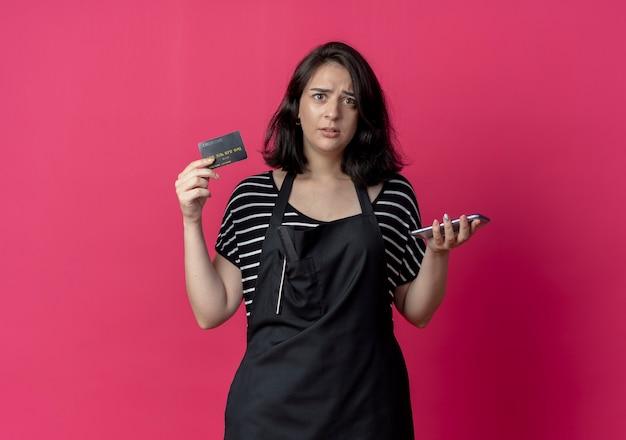 ピンクで混乱しているスマートフォンとクレジットカードを保持しているエプロンの若い美しい女性の美容師