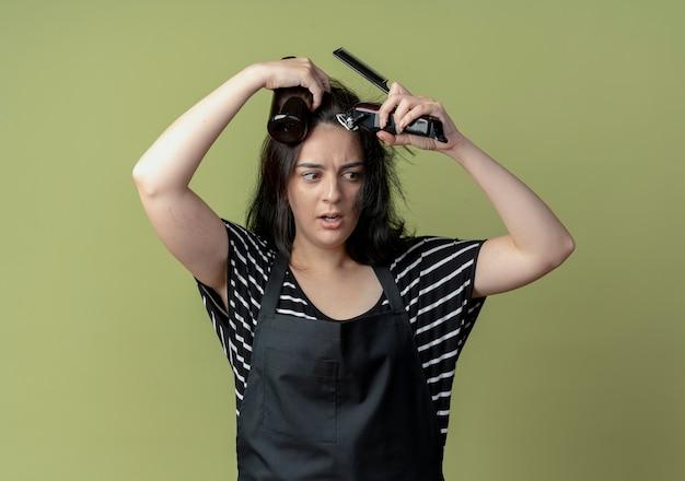 Молодая красивая женщина-парикмахер в фартуке держит спрей и расческу, собираясь подстричь волосы триммером на свету