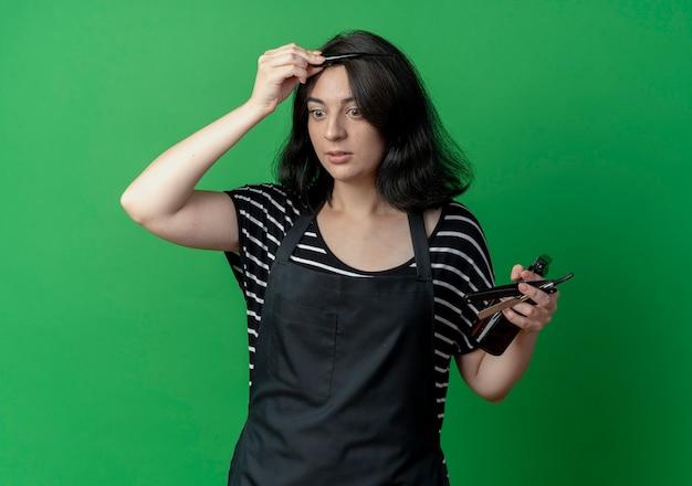 Молодая красивая женщина-парикмахер в фартуке держит спрей и бритву, расчесывая волосы по зеленому