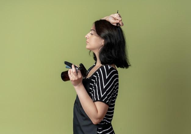 스프레이 빗과 면도칼을 들고 앞치마에 젊은 아름다운 여성 미용사 빛 벽에 옆으로 서