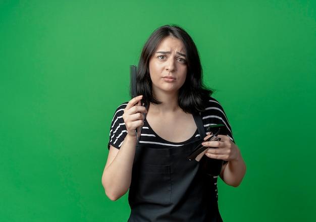 Молодая красивая женщина-парикмахер в фартуке держит расческу и бритву с рукой, задавая вопрос, стоя над зеленой стеной