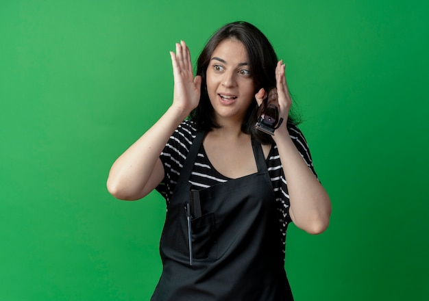 緑の壁の上に立って混乱して脇を見てトリマーを保持しているエプロンの若い美しい女性の美容師