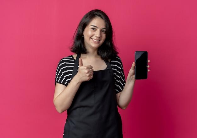 エプロンの若い美しい女性の美容師は、ピンクの上に親指を表示して笑顔のスマートフォンを示しています