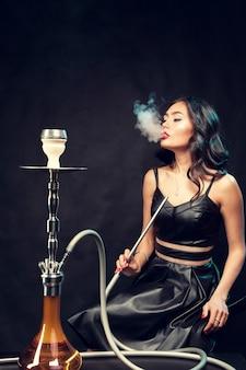 Молодая красивая женщина в черном платье курит и выдыхает кальян