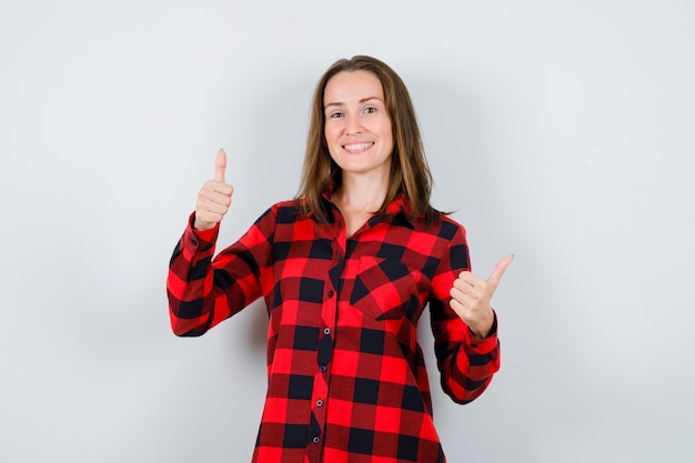 Молодая красивая женщина в повседневной рубашке показывает палец вверх и выглядит блаженным, вид спереди.