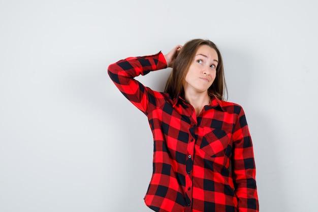 캐주얼 셔츠를 입은 젊고 아름다운 여성은 머리 뒤에 손을 얹고 멀리 바라보고 사려깊은 전면 전망을 보고 있습니다.
