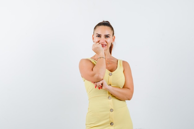 Молодая красивая женщина в платье подпирая подбородок под рукой и радостный вид спереди.