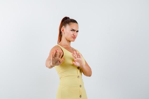 拒否ジェスチャーを示し、うんざりしている、正面図を示すドレスを着た若い美しい女性。
