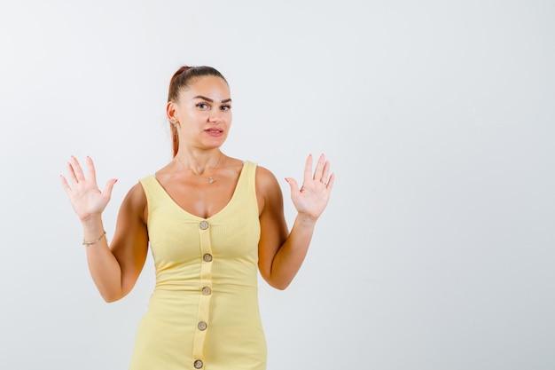 Молодая красивая женщина в платье показывает жест капитуляции и выглядит сбитым с толку, вид спереди.