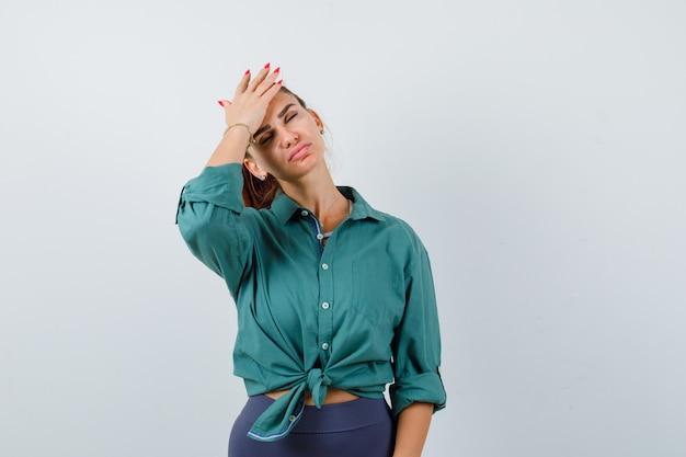 額に手を保ち、眠そうな、正面図の緑のシャツを着た若い美しい女性。