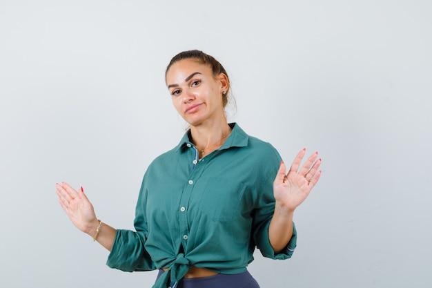 Молодая красивая женщина в зеленой рубашке показывает жест капитуляции и недоумевает, вид спереди.