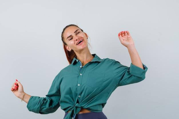 勝者のジェスチャーを示し、陽気に見える緑色のシャツを着た若い美しい女性、正面図。