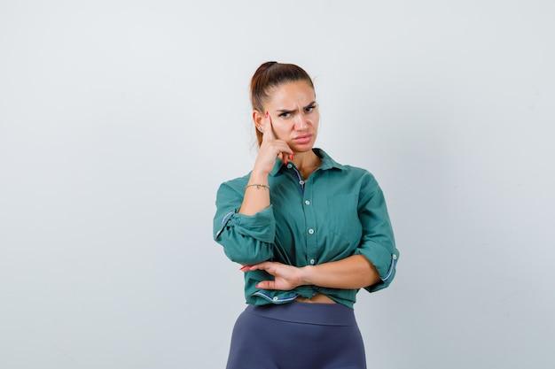 緑のシャツを着た若い美しい女性がポーズを考えて立って困惑している、正面図。